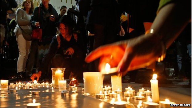 A woman lights a candle for the prisoners to be executed in Indonesia, during a vigil in Sydney