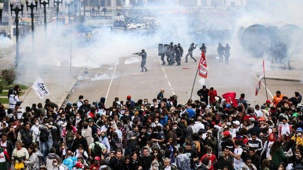 Policemen fire rubber bullets and tear gas against teachers during a protest in Curitiba in Parana state April 29, 2015.