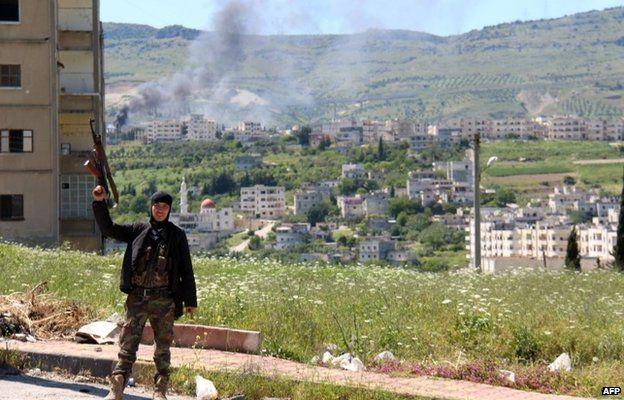 Syrian rebel fighters holds his rifle aloft near Jisr al-Shughour (25 April 2015)