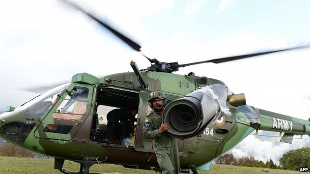 An Indian Army helicopter pilot unloads relief aid in the village of Laprak, in northern-central Gorkha district (30 April 2015)