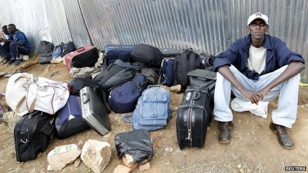 A student from a Burundi university sits next to bags of other students as they camp outside the U.S. embassy in the capital Bujumbura, May 1, 2015.