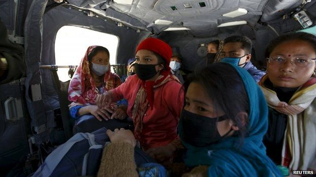Earthquake victims airlifted from Sindhupalchok District sit inside an army helicopter while on their way to Kathmandu
