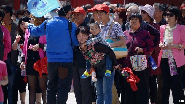 A family (C) looks on after visiting the Forbidden City in Beijing on 3 May 2015.