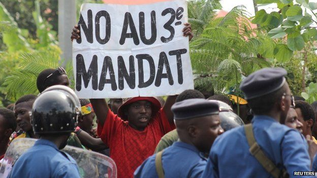 """A protester holds a placard as they demonstrate against the ruling CNDD-FDD party""""s decision to allow Burundi President Pierre Nkurunziza to run for a third five-year term in office"""