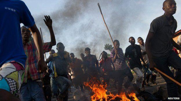 Protestors run across a fire towards police lines in the Musaga neighbourhood of Bujumbura, on May 4, 2015