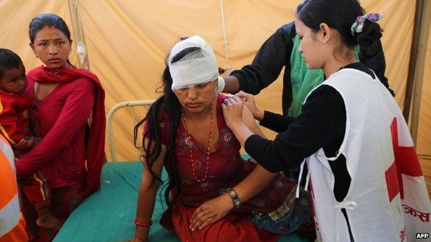 Nepal Red Cross volunteer and nurse Alina Shaestha (R) treating a wounded woman in the village of Chautara in Sindupolchowk.