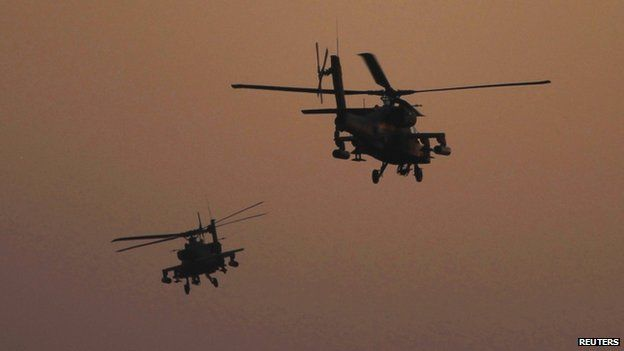 Apache helicopters flying at dusk