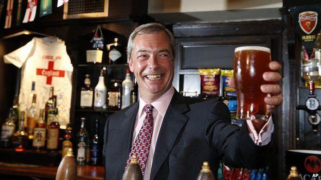 Nigel Farage raises a pint of ale in a pub