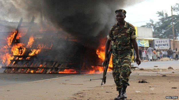 A soldier walks past a barricade erected on the road by demonstrators protesting against the ruling CNDD-FDD party's decision to allow Burundian President Pierre Nkurunziza to run for a third five-year term in office, in Bujumbura, 7 May 2015