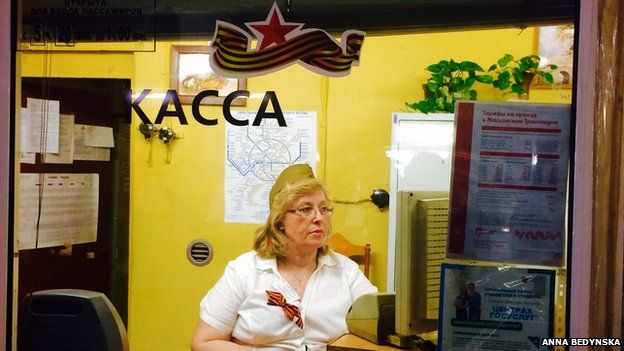 Cashier at the Moscow underground wearing a green oblong hat