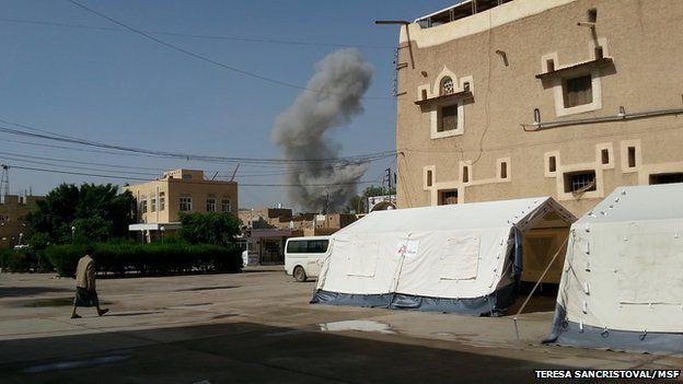 Smoke rises in distance behind buildings in Saada on 9 May 2015