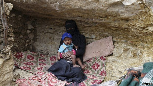 """An internally displaced woman sits with a child in a cave in the district of Khamir of Yemen""""s north-western province of Amran 9 May 2015"""