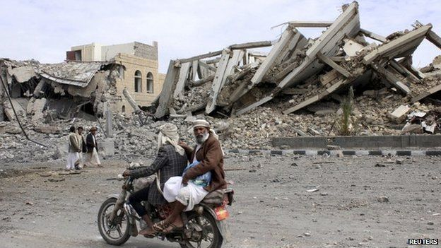 """People ride on a motorcycle as they pass by a police headquarters destroyed by a Saudi-led air strike in Yemen""""s north-western city of Saada 7 May 2015"""