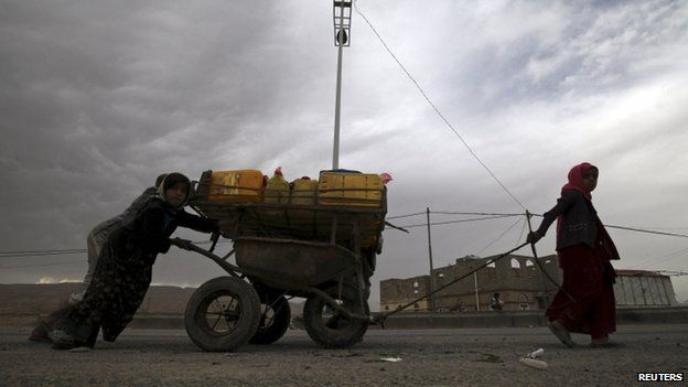 """Internally displaced children transport water with a cart in the district of Khamir of Yemen""""s north-western province of Amran May 9, 2015"""
