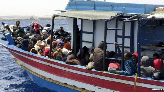 Migrants who attempted to sail to Europe sit in a boat carrying them back to Libya, 6 May 2015