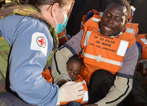 Royal Navy medical assistant cares for a four-year-old migrant who has just been rescued