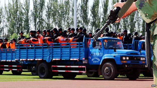 This picture taken on 27 May 2014 shows security forces standing behind the accused wearing orange vests on trucks during a mass sentencing in Ili prefecture, northwest China's Xinjiang region.