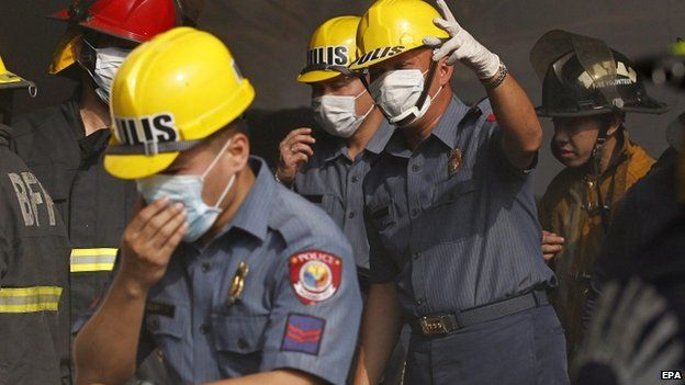Filipino policemen wearing facemasks inspect a burnt warehouse following a fire in Valenzuela city, east of Manila, Philippines, 13 May 2015