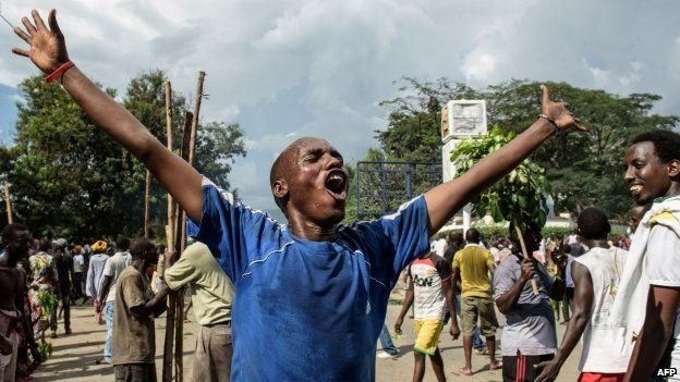 Man raises his arms in celebration in the streets of Bujumbura. 13 May 2015