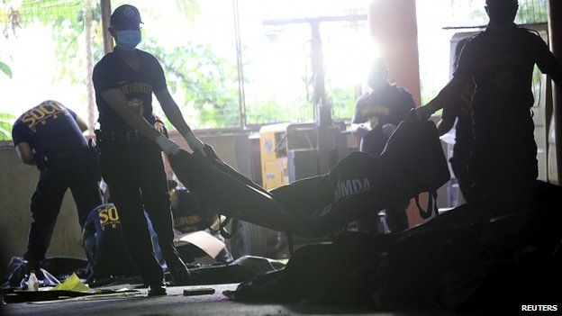 Members of the Scene of the Crimes Operatives bring in bags of charred bodies of the workers at municipal hall in Valenzuela city, north of Manila on 14 May 2015.