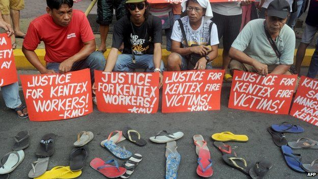 Protesters hold placards, while displaying sandals on the ground, during a rally to call for justice for the victims of a fire that gutted a footwear factory the day before, in Manila on 14 May 2015.