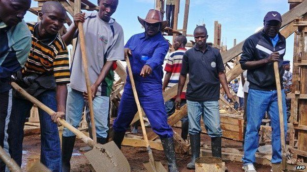Burundi's President, Pierre Nkurunziza (C) helps on the construction site of a school in the province of Ngozi in northern Burundi on September 12, 2013