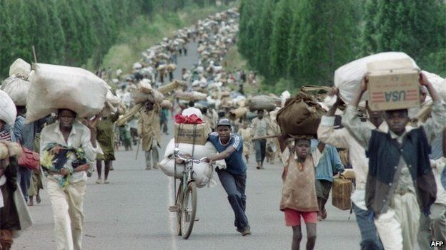 Tens of thousands of Rwandan Hutu refugees carry their belongings as they flee towards the Tanzanian border from the refugee camps at Magara, near the northern Burundian town of Ngozi on 31 March 1995