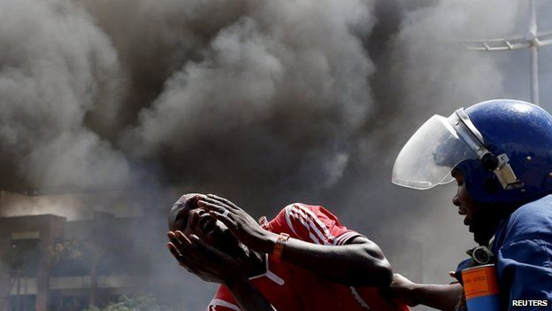 """A detained protester cries in front of a burning barricade during a protest against President Pierre Nkurunziza""""s decision to run for a third term in Bujumbura, Burundi on 13 May 2015."""