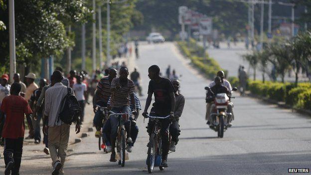 People ride bicycles in a street in Bujumbura, Burundi, on 15 May 2015.