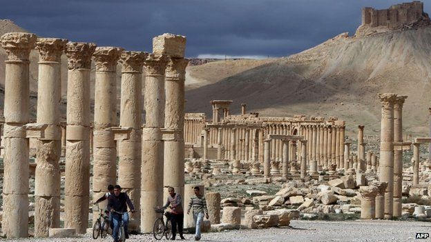 March 14, 2014 shows Syrian citizens riding their bicycles the ancient oasis city of Palmyra, 215 kilometres northeast of Damascus, on 14 March 2014