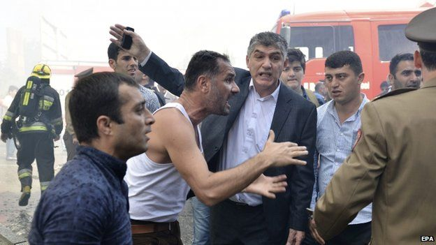 Angry Azeris argue with fire fighters and police at the scene of a burning 16-storey residential building in Baku, Azerbaijan 19 May 2015