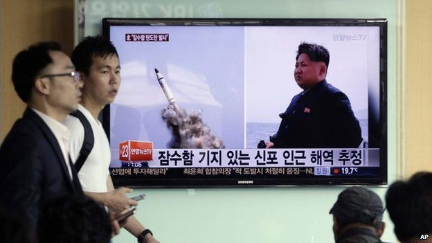 Men pass by a TV news programme displaying images purporting to show a missile test in North Korea