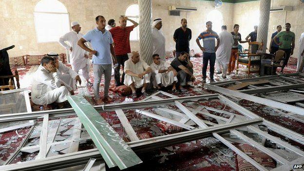 Saudi men gather around debris following the blast inside the mosque in the coastal town of Qatif - 22 May 2015