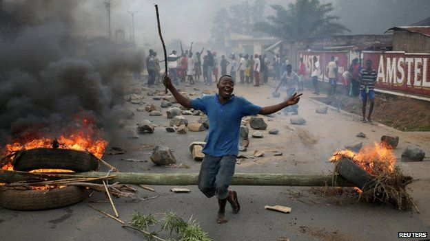 """A protester dances in front of a barricade during a protest against Burundi""""s President Pierre Nkurunziza and his bid for a third term in Bujumbura, Burundi, May 22, 2015"""