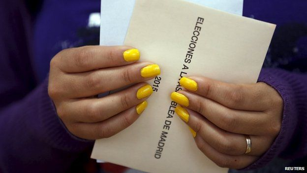 A woman holds her ballots as she votes at a polling station during regional and municipal elections in Madrid, Spain, May 24, 2015