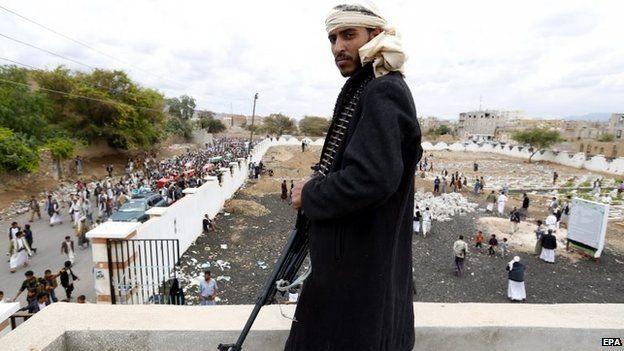 Houthi rebel looks at the burials of comrades killed in Saudi-led coalition air strikes in Sanaa, Yemen (24 May 2015)