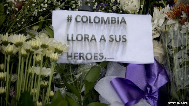 """A message reading """"Colombia weeps for its heroes"""" is seen between flowers outside a military base in Medellin on 17 April, 2015."""
