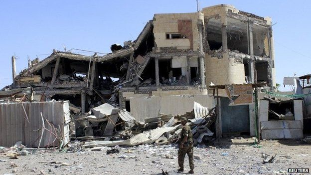 Houthi rebel fighter walks past a house damaged in a Saudi-led coalition air strike in the city of Saada (24 May 2015)