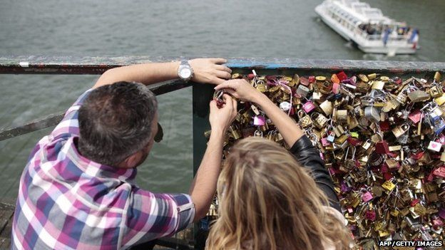 """A couple locks a padlock on the """"Pont des Arts"""" on May 29, 2015 in Paris"""