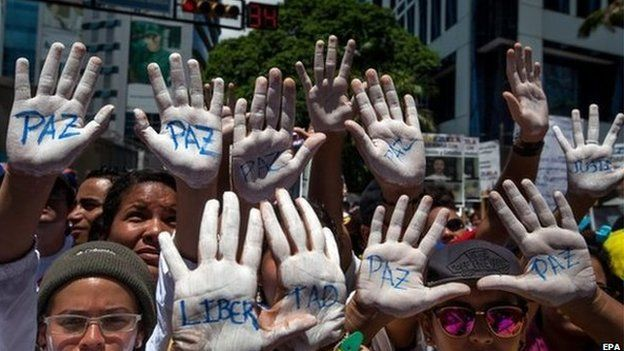 """People show their hands painted in white and the word """"Peace"""" during a demonstration against the Venezuelan government, in Caracas, Venezuela, 30 May 2015."""