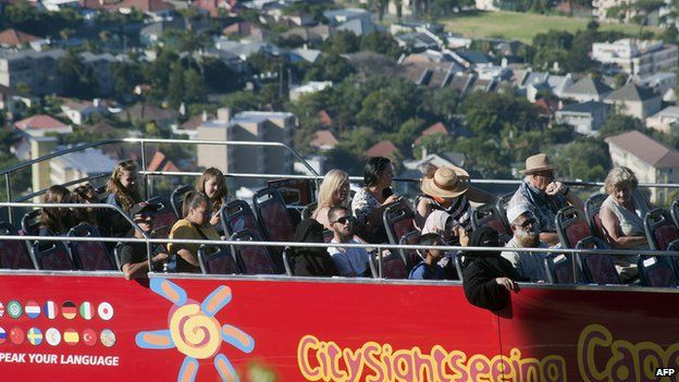 People take an open-top bus tour on January 11, 2014 in Cape Town.