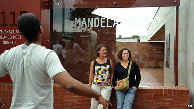 Tourists pose for a photo in front of the Mandela House, Nelson Mandela's former house, in Soweto on March 29, 2013.