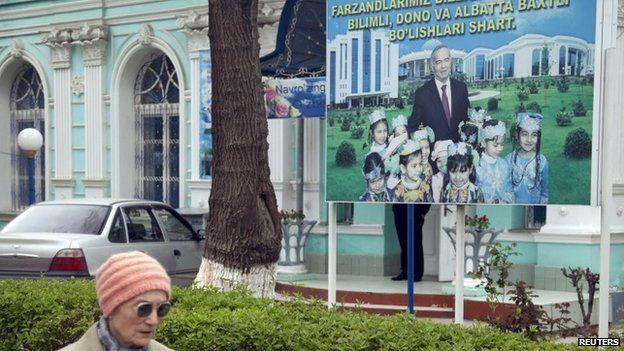 A woman walks past an election board of Uzbekistan's President Islam Karimov near a polling station in Tashkent (29 March 2015)