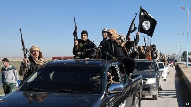 Islamic State militants pass by a convoy in Tel Abyad town, north-eastern Syria (04 May 2015)