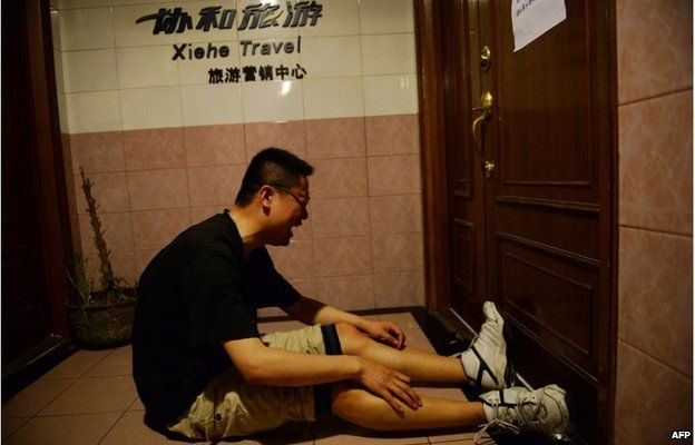 A relative of missing passengers who were on a ship which sank in the powerful Yangtze river the night before reacts after hearing news of the sinking outside a travel agency in Shanghai on 2 June 2015