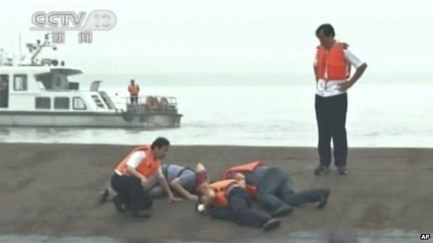 Rescue workers listen for a response to their tapping on the hull of a capsized ship on the Yangtze River (02 June 2015)