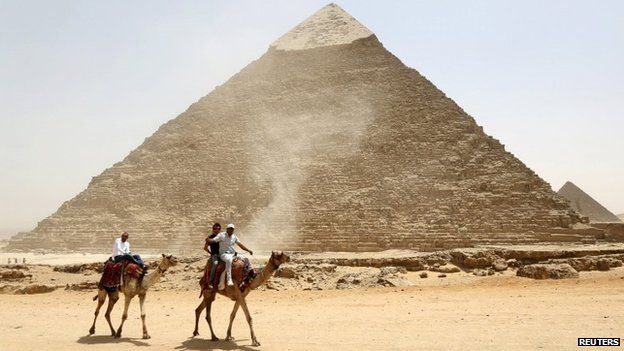 Men ride camels in from of the pyramids at Giza