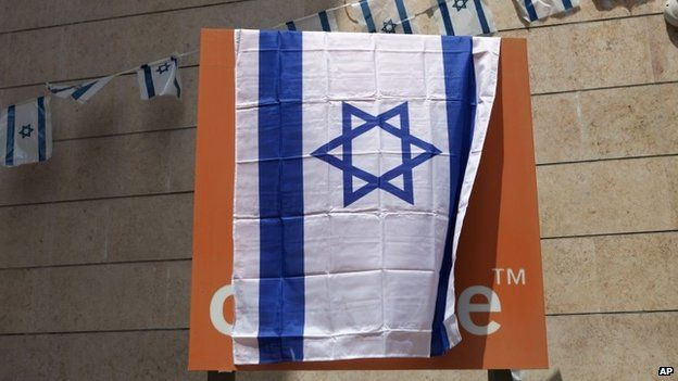"""The Orange company logo is seen covered with an Israeli flag at the """"Partner Orange"""" Communications Company""""s offices in the city of Rosh Haain, Israel, Thursday, June 4, 2015."""