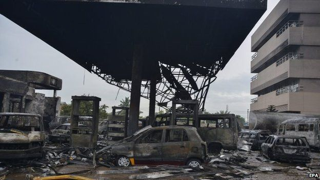 Destroyed vehicles at the scene of a petrol station fire in Accra, Ghana, 04 June 2015