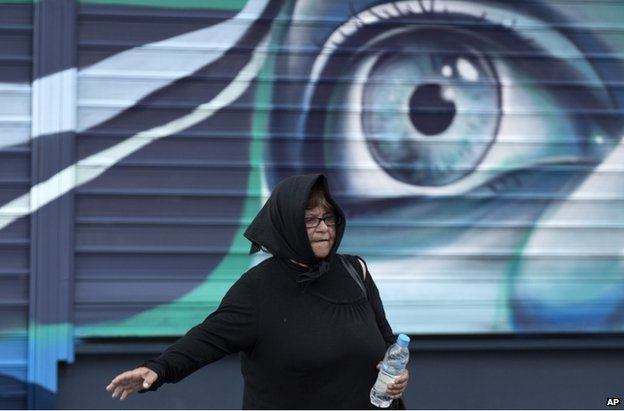 A woman walks past graffiti by street artist Achilles outside a shop, in Athens, Greece, on Thursday 4 June 2015